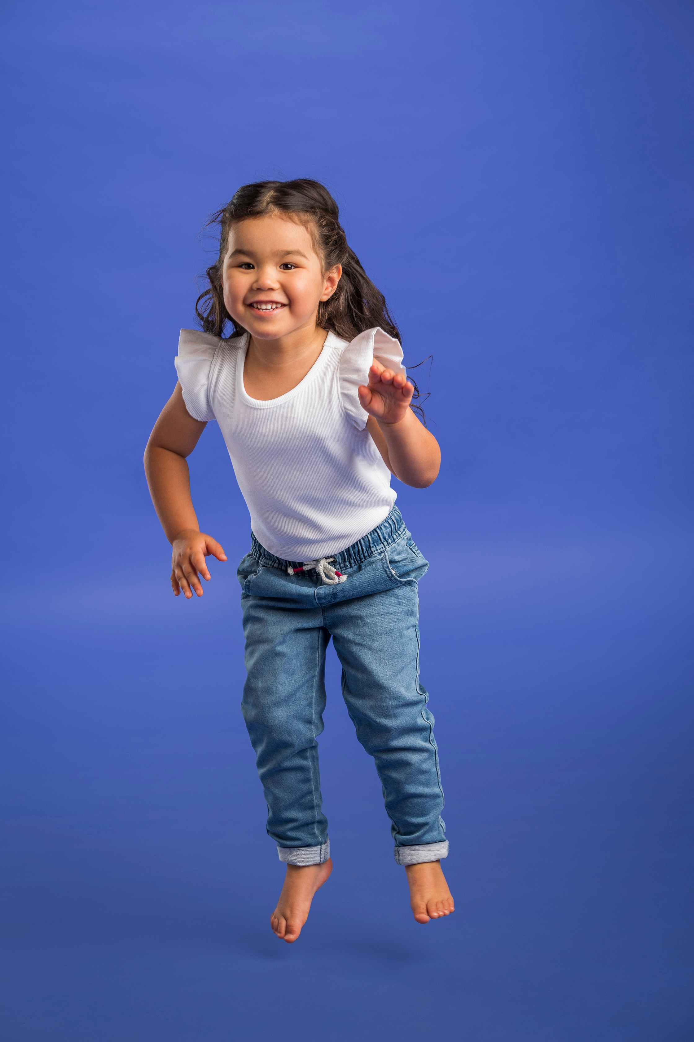Sora, a four year old girl who was born with Leber's congenital amaurosi, jumps for the photoshoot for Jeans and Genes.
