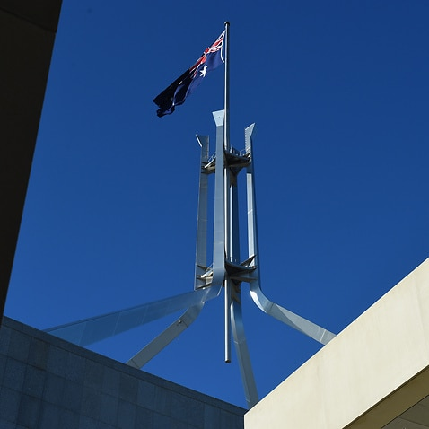 The Australian flag is seen above Parliament House in Canberra.