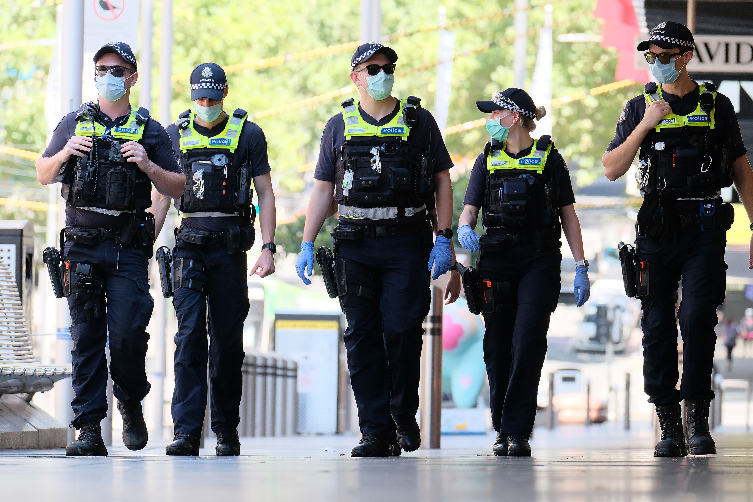 Victorian Police officers walk around  Melbourne's CBD , Monday, February 15, 2021. Victorians are in lockdown for the third time amid fears the highly infectious UK strain of coronavirus has spread in the community. (AAP Image/Luis Ascui) NO ARCHIVING