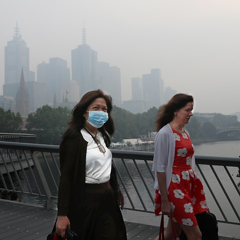 People wear breathing masks to protect themselves from a thick smoke haze that hangs over Melbourne from the bushfires. Tuesday, 14 January, 2020.