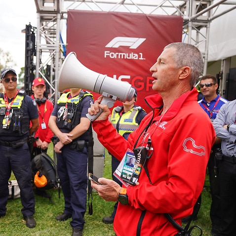 An Australian Grand Prix official tells the crowd of spectators waiting at the gate that the event has been cancelled.