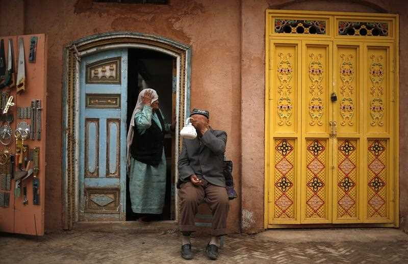 A man of the Uighur ethnic group has tea while his wife looks on in the old town of Kashgar, Xinjiang Uighur Autonomous Region, China, 24 May 2013. (AAP)