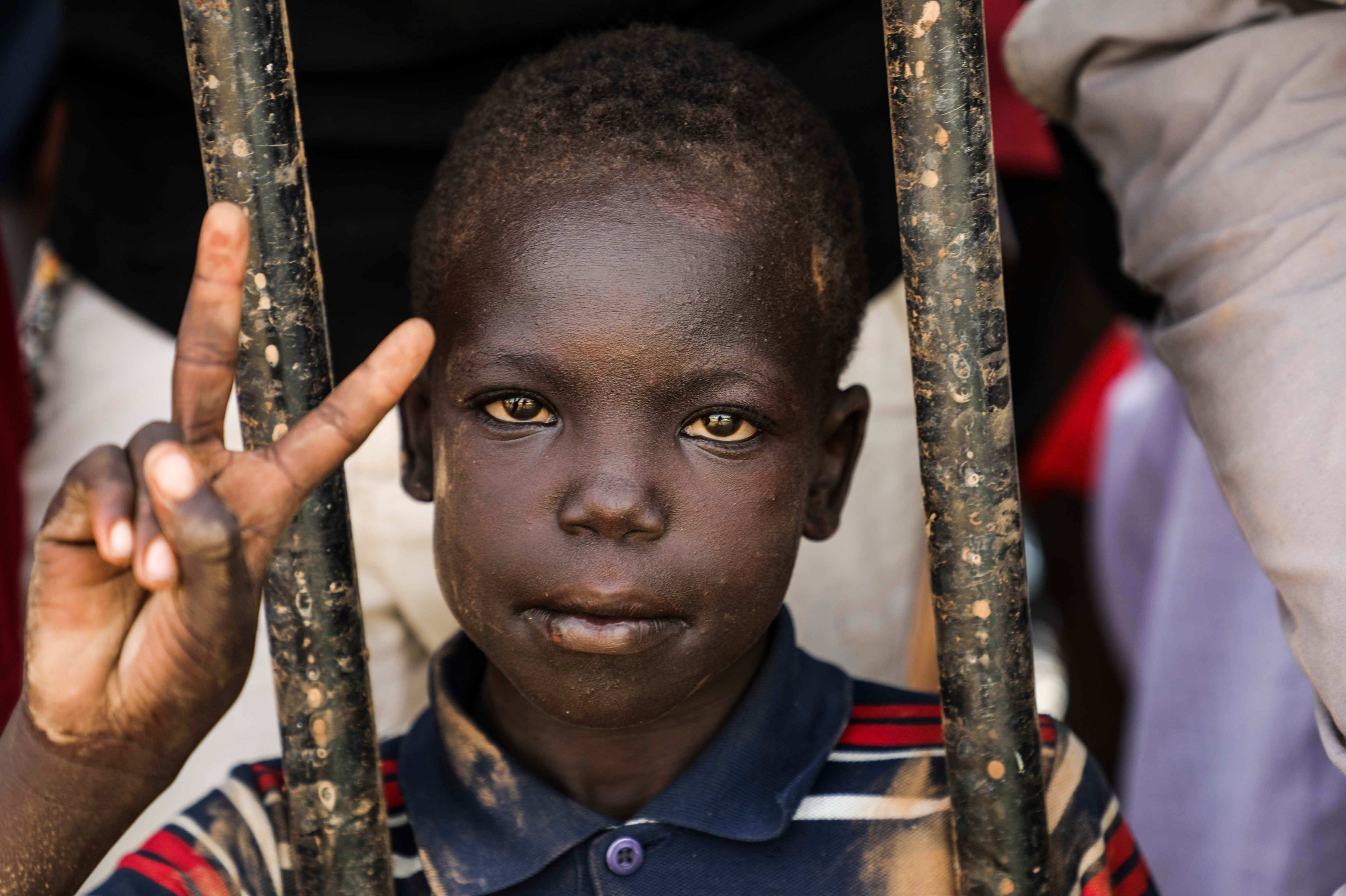 A Sudanese boy flashes the victory sign during the protest.