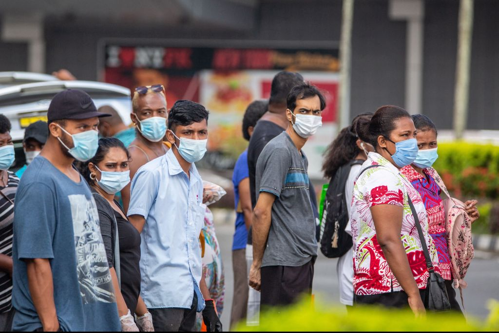 Residents wearing face masks waiting to cross the main road in the Fijian capital Suva.