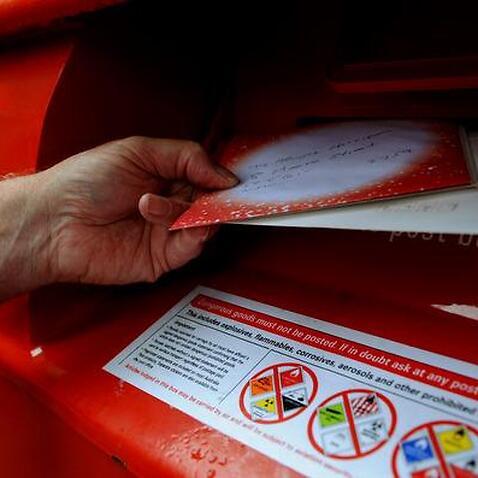 A man posts mail at an Australia Post box
