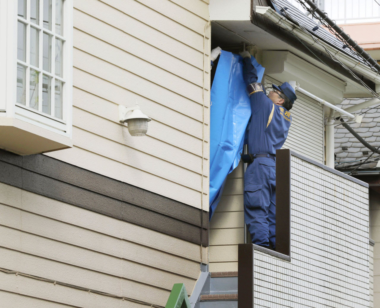 A police officer places a blue sheet on part of an apartment house in Zama, Kanagawa Prefecture on Oct. 31, 2017 where police found nine dismembered bodies.
