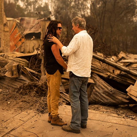 Business owner Sally Anne Wilson (left) stands in front of her destroyed shop with her partner Christopher Lee in Cobargo, NSW.