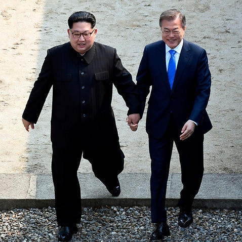 North Korean leader Kim Jong Un and South Korean President Moon Jae-in cross the military demarcation line at the border village of Panmunjom on 27 April, 2018.
