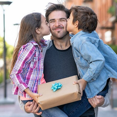 Loving son and daughter kissing daddy on the cheek while he carries them both with a present for father's day