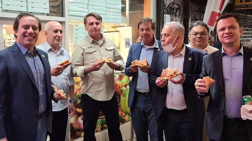 Brazil President Jair Bolsonaro (third from left) eating pizza on the sidewalk in New York City.