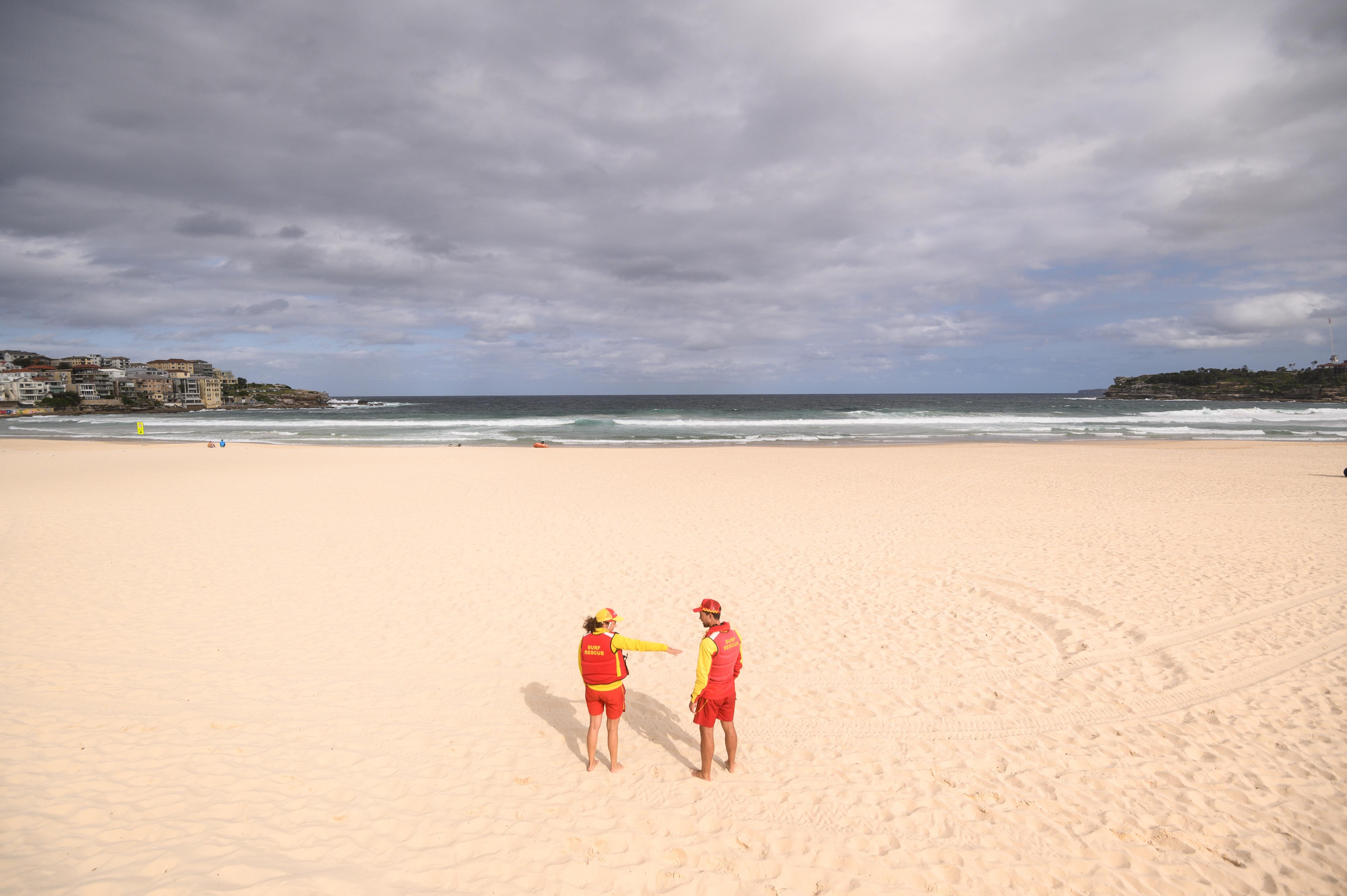 Surf lifesavers on an empty Bondi Beach following its closure in Sydney, Saturday, March 21, 2020.