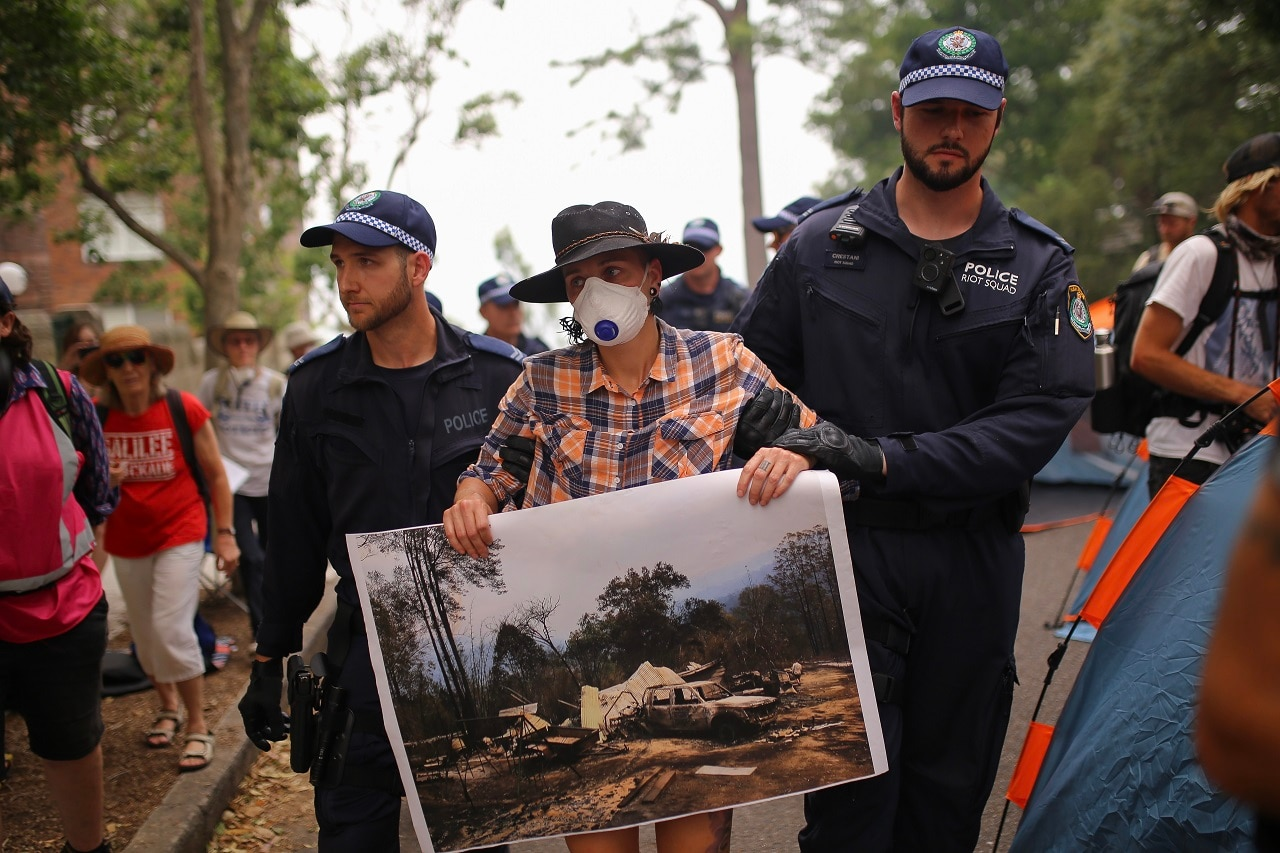 A protester holding a photograph of property destroyed by bushfire is arrested outside of Kirribilli House.