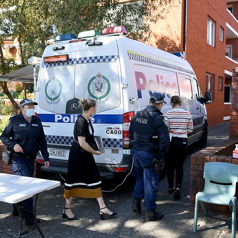 Health workers and Police officers are seen at a unit block under lockdown, in Campsie, south west of Sydney, Friday, August 20, 2021. (AAP Image/Dan Himbrechts) NO ARCHIVING
