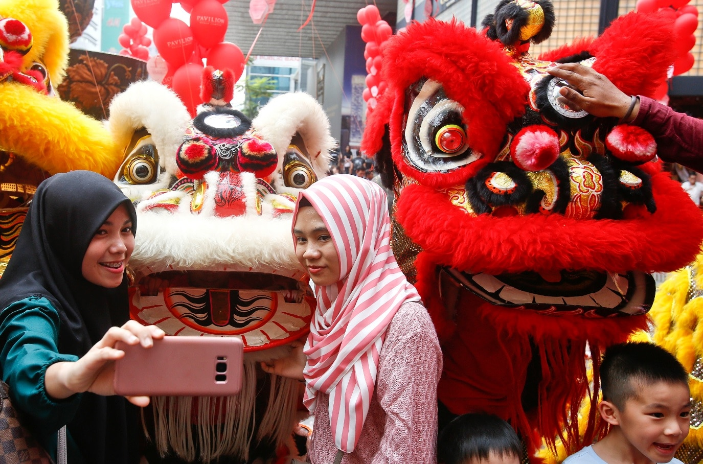 Muslims women take pictures with the lion dance at a shopping mall ahead of the Lunar New Year celebrations in Kuala Lumpur, Malaysia, Saturday, Feb. 10, 2018.