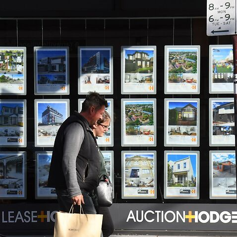 A couple walks past a real estate agent's window advertising houses for sale and auction in Melbourne on May 1, 2019