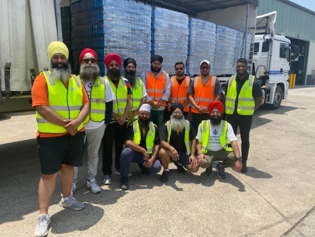 Members of the Sikh community stand in front of a truck filled with water supplies.