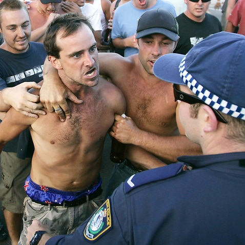 A man threatens police at Cronulla Beach during the riots.