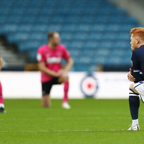 Ryan Woods of Millwall kneels opposite Derby players before a Championship match