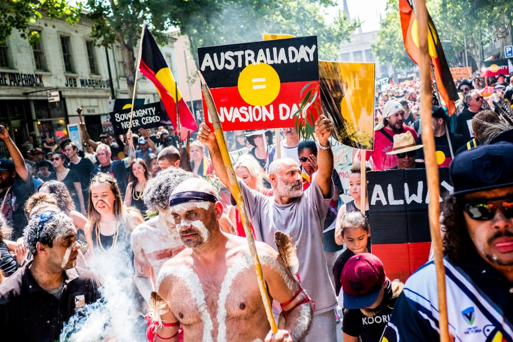 Protestors holding placards march during a protest by Aboriginal rights activist on Australia Day in Melbourne, Australia 26 January 2018.