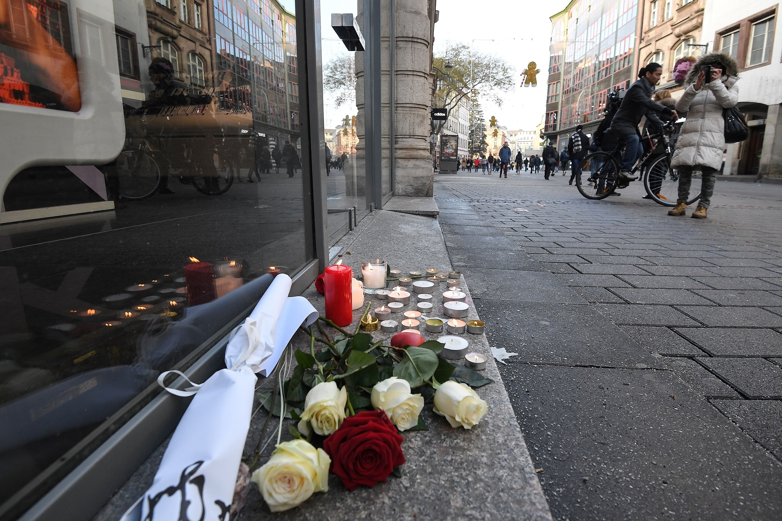Flowers and candles are seen on the pavement the day after a deadly shooting in central Strasbourg.