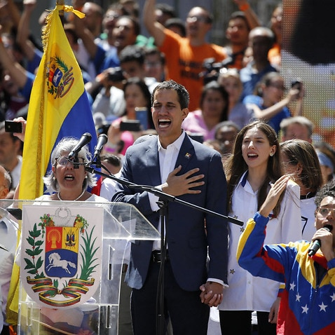 Venezuela' self-proclaimed interim president Juan Guaido sings the national anthem as thousands march against President Nicolas Maduro.