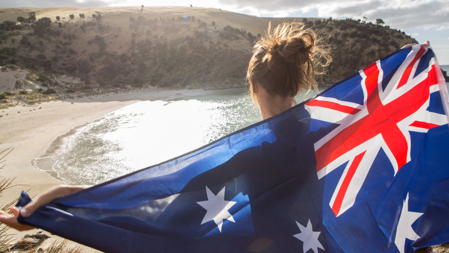 Cheerful young woman stands on a cliff above a beach in Kangaroo Island holding an Australian's flag