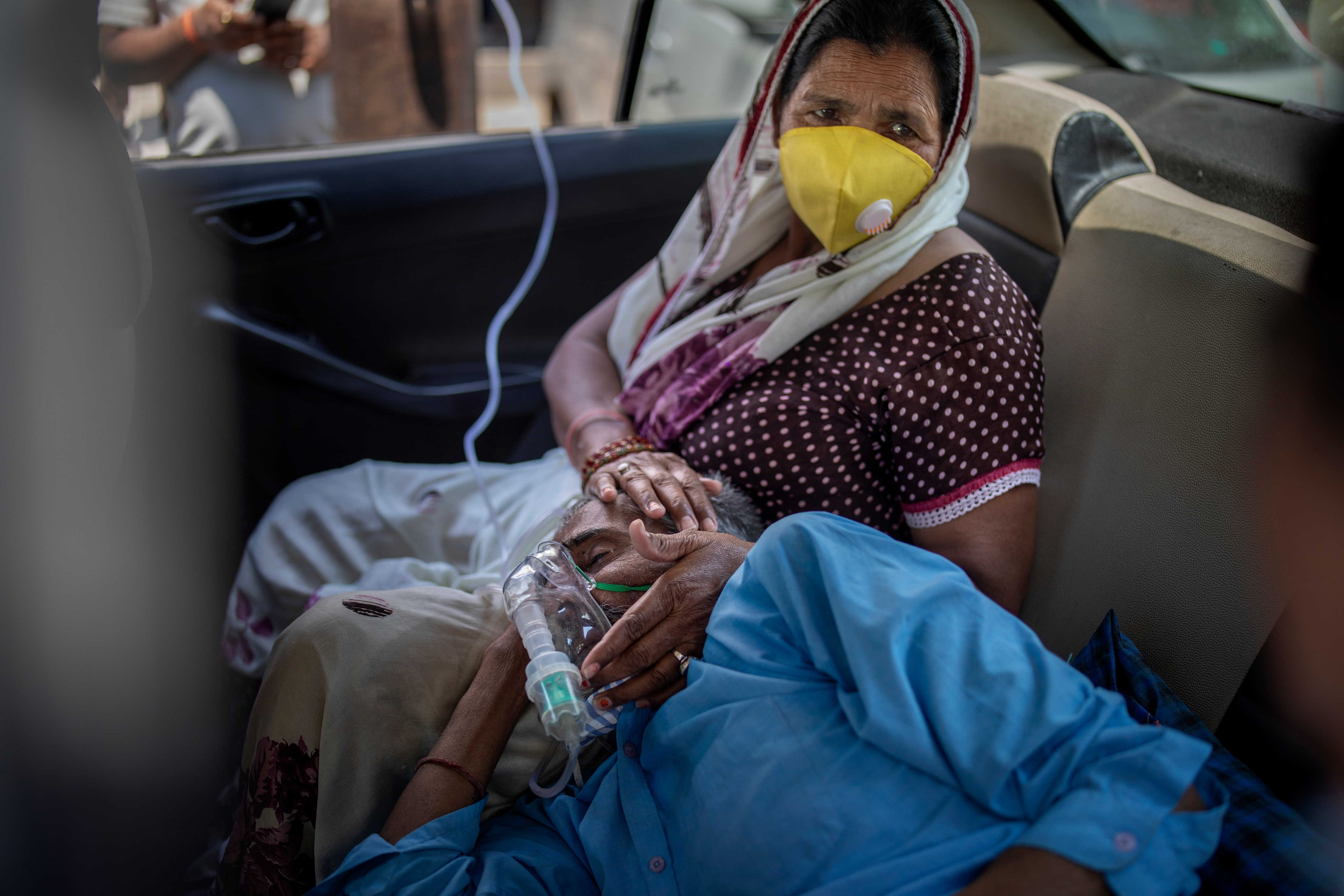 A patient breathes with the help of oxygen provided by a Gurdwara, Sikh place of worship, inside a car in New Delhi, India.