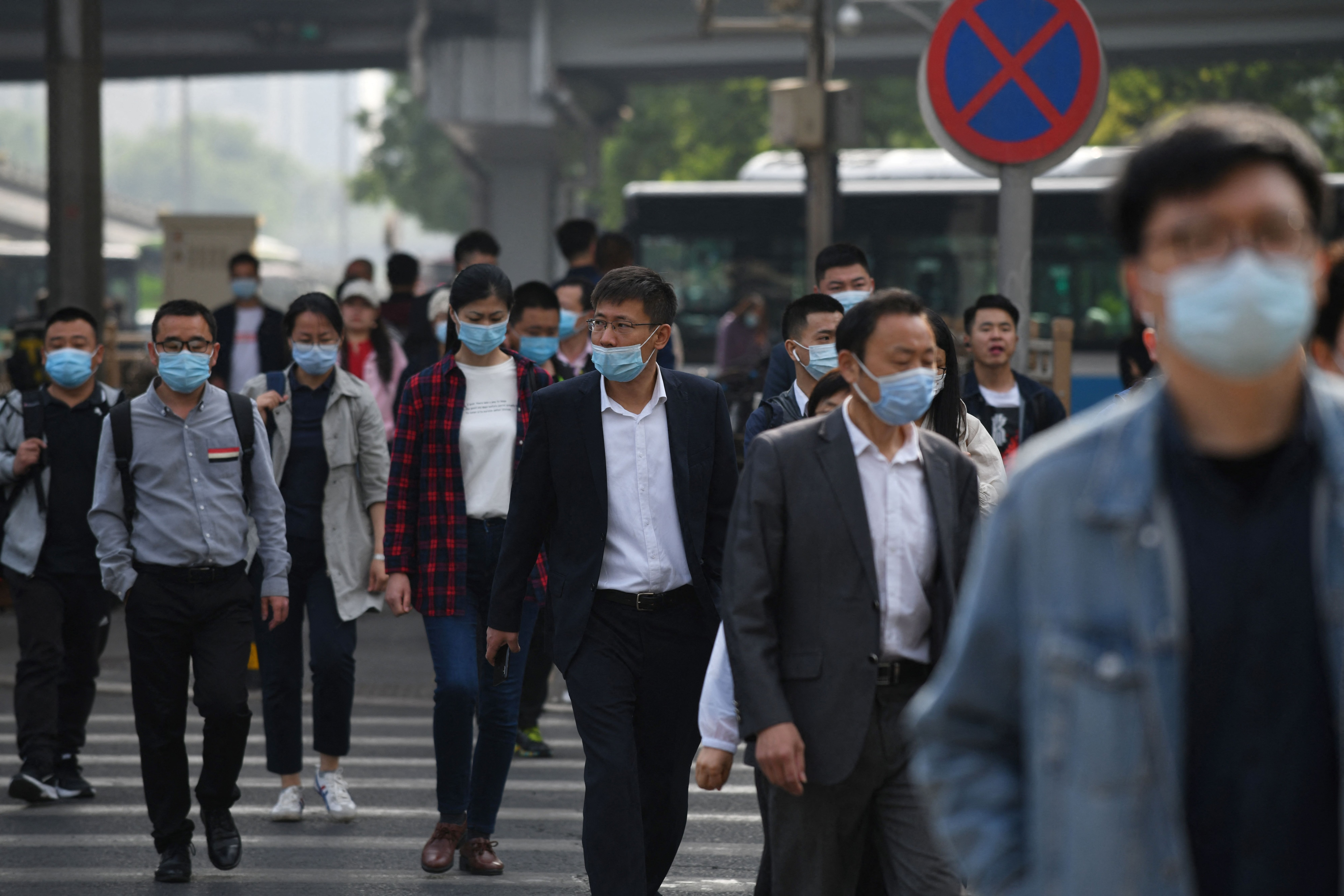 Commuters cross a street during morning rush hour in Beijing on 11 May, 2021.