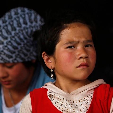 A girl and women of the Uighur ethnic group look on in Yopurga village of Kashgar, Xinjiang Uighur Autonomous Region, China