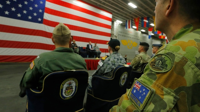 A member of the Australian Army sits in the audience alongside a U.S. flag as the backdrop of a ceremony marking the start of Talisman Saber 2017