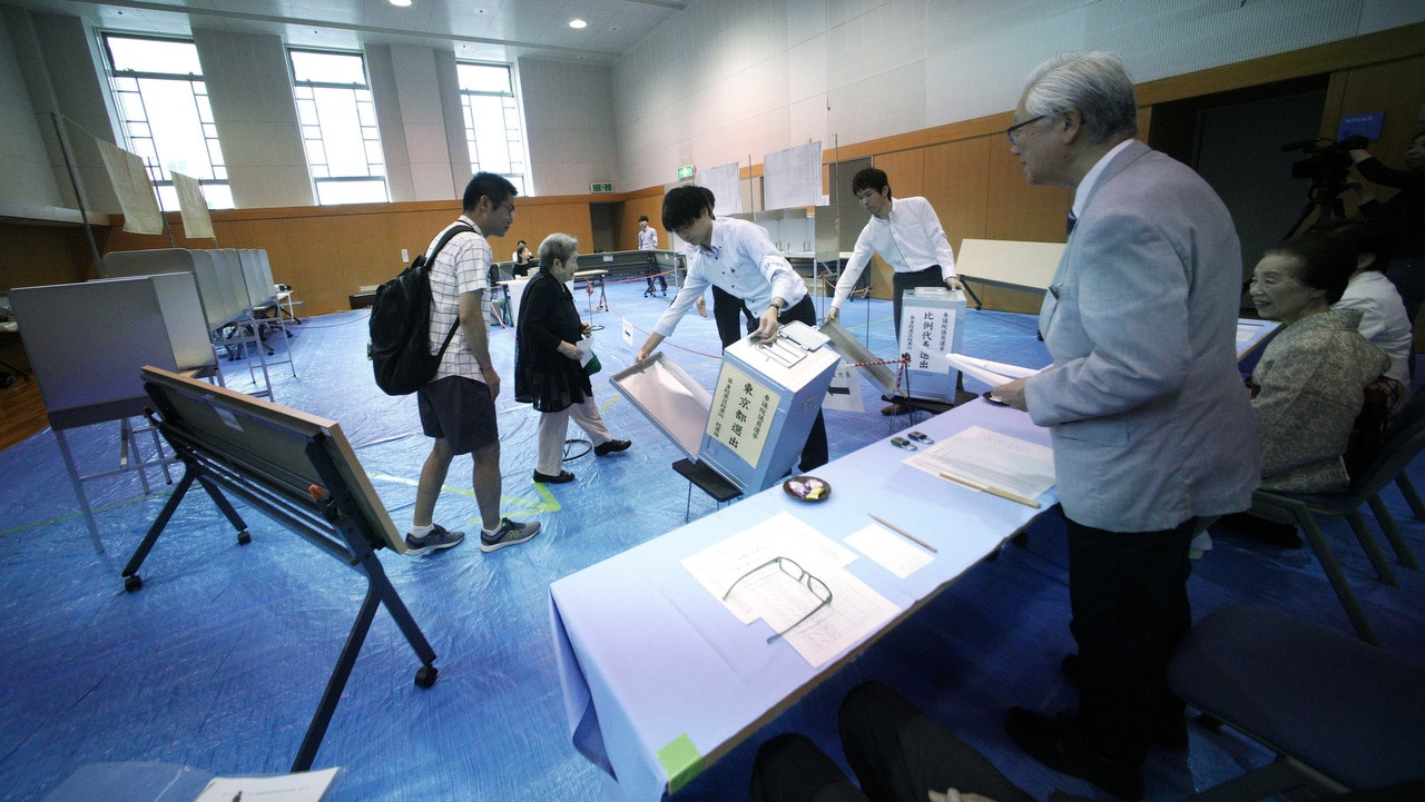 Representatives of a local election administration commission show the earliest two voters the empty ballot box before they cast their votes.