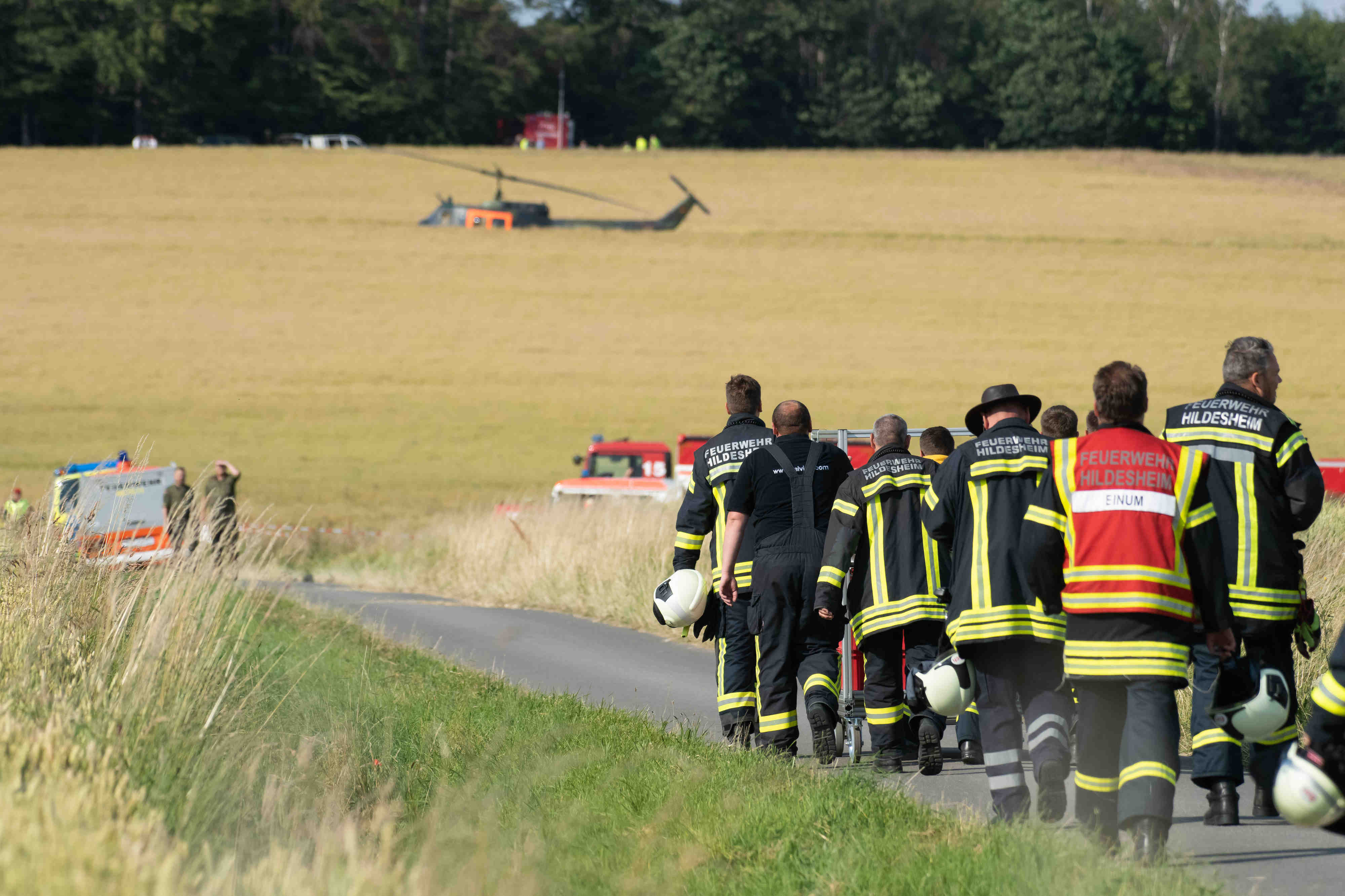 Firefighters walk along a path to the crash site of a German Armed forces helicopter.