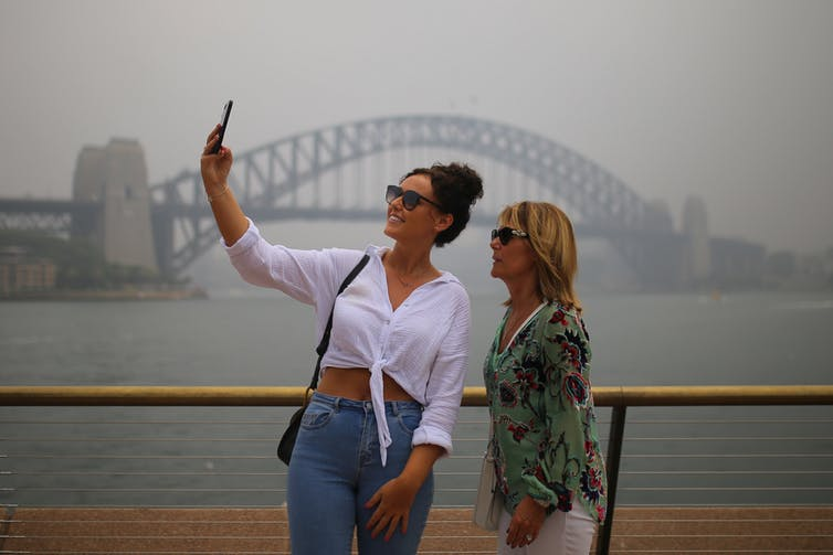 Tourists take selfies against a smoke-filled Sydney Harbour last month.