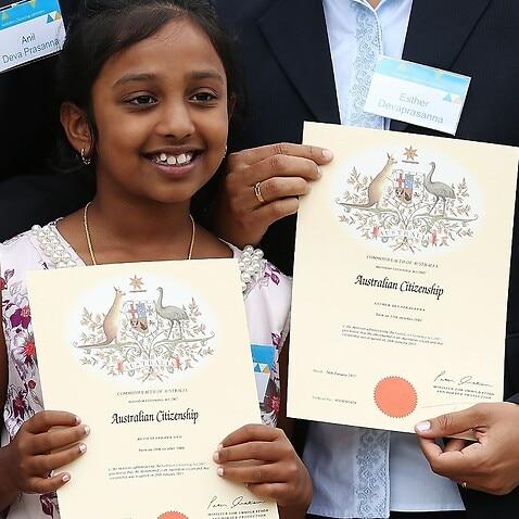 An Indian child receives Australian Citizenship Certificate.