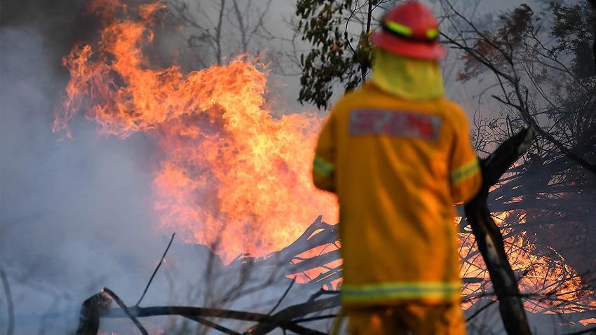 A firefighter defends a property in Torrington, near Glen Innes,