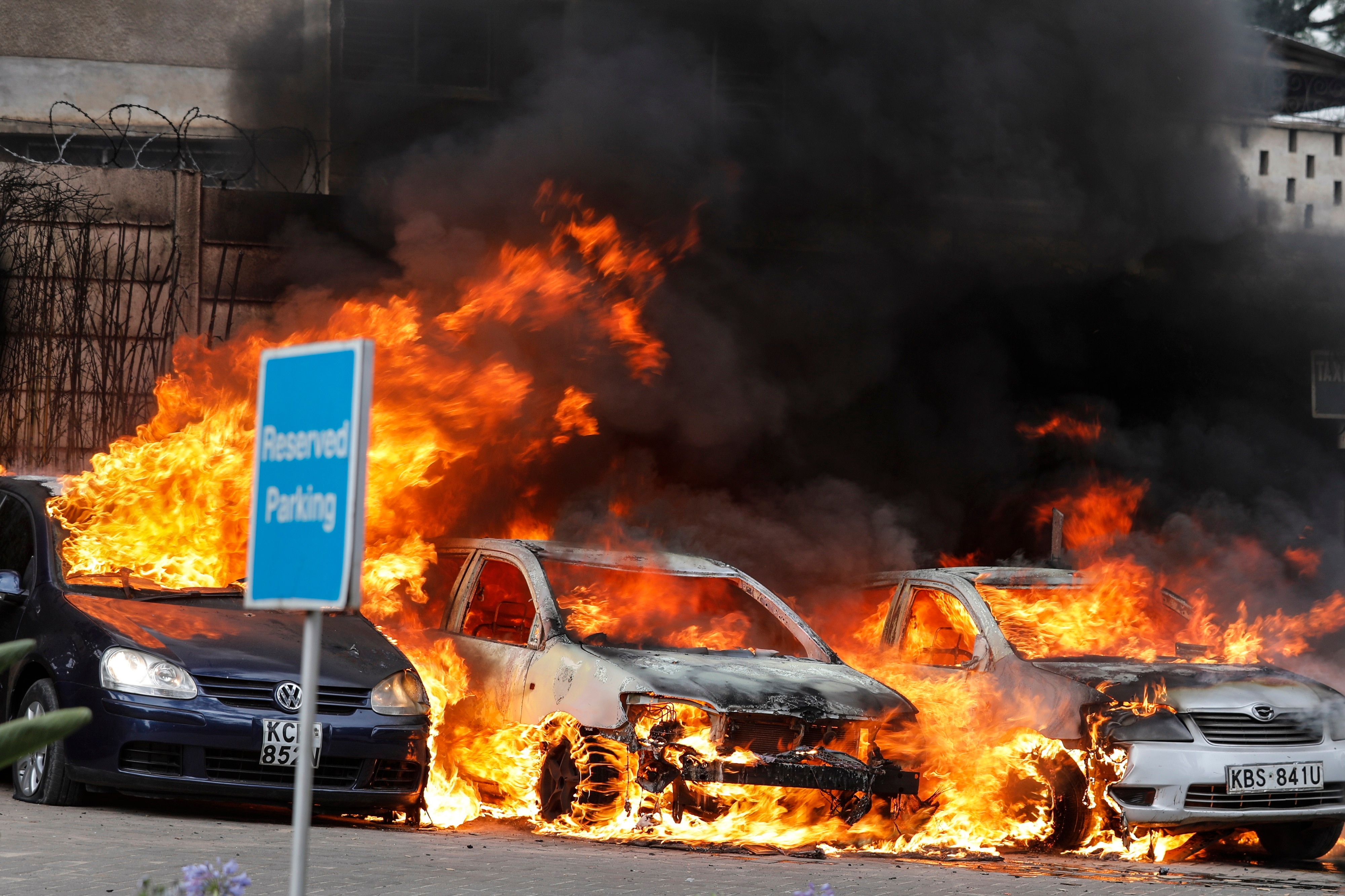 Cars burn at the parking lot during an ongoing gunfire and explosions in Nairobi, Kenya.