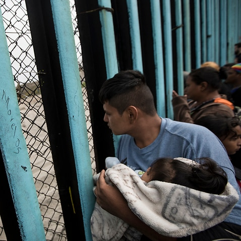 A member of the Central American migrant caravan, holding a child, looks through the border wall toward a group of people gathered on the U side, as he stands on the beach where the border wall ends in the ocean, in Tijuana, Mexico