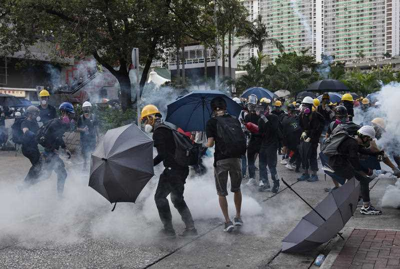 Protesters take cover as police and security forces fire tear gas during clashes in Hong Kong.
