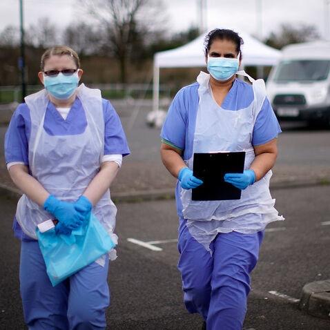 医療従事者は、イギリスのウォルバーハンプトンにあるコロナウイルス検査サイトで次の患者を待ちます。