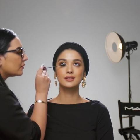 A MAC makeup artist demonstrates a look on a model