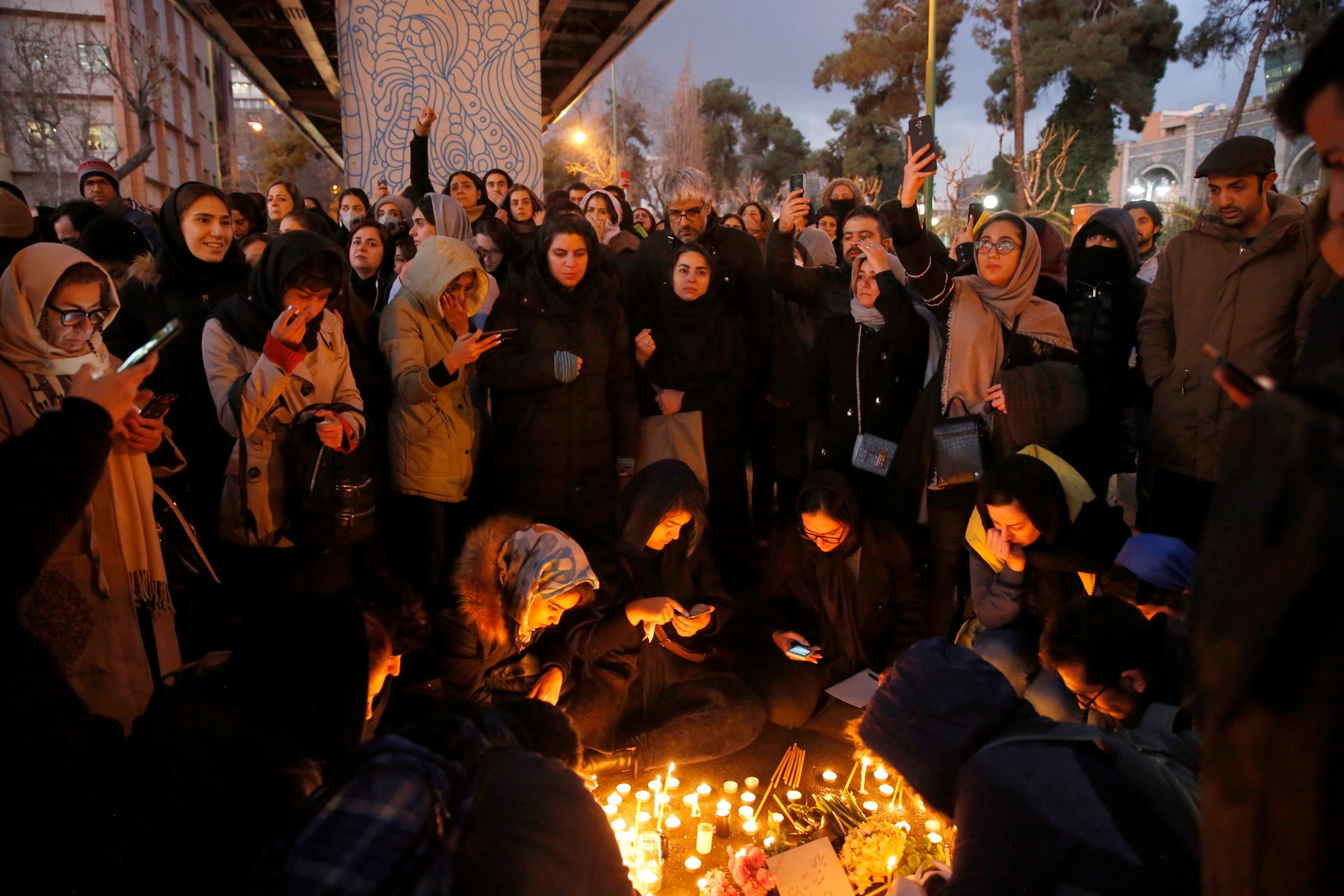 Iranians light candles for victims of Ukraine International Airlines Boeing 737-800 during as they protest in front of the Amir