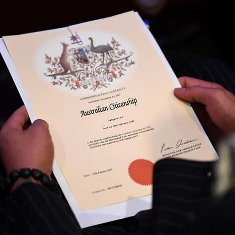 An Australian citizenship recipient holds his certificate during a citizenship ceremony.