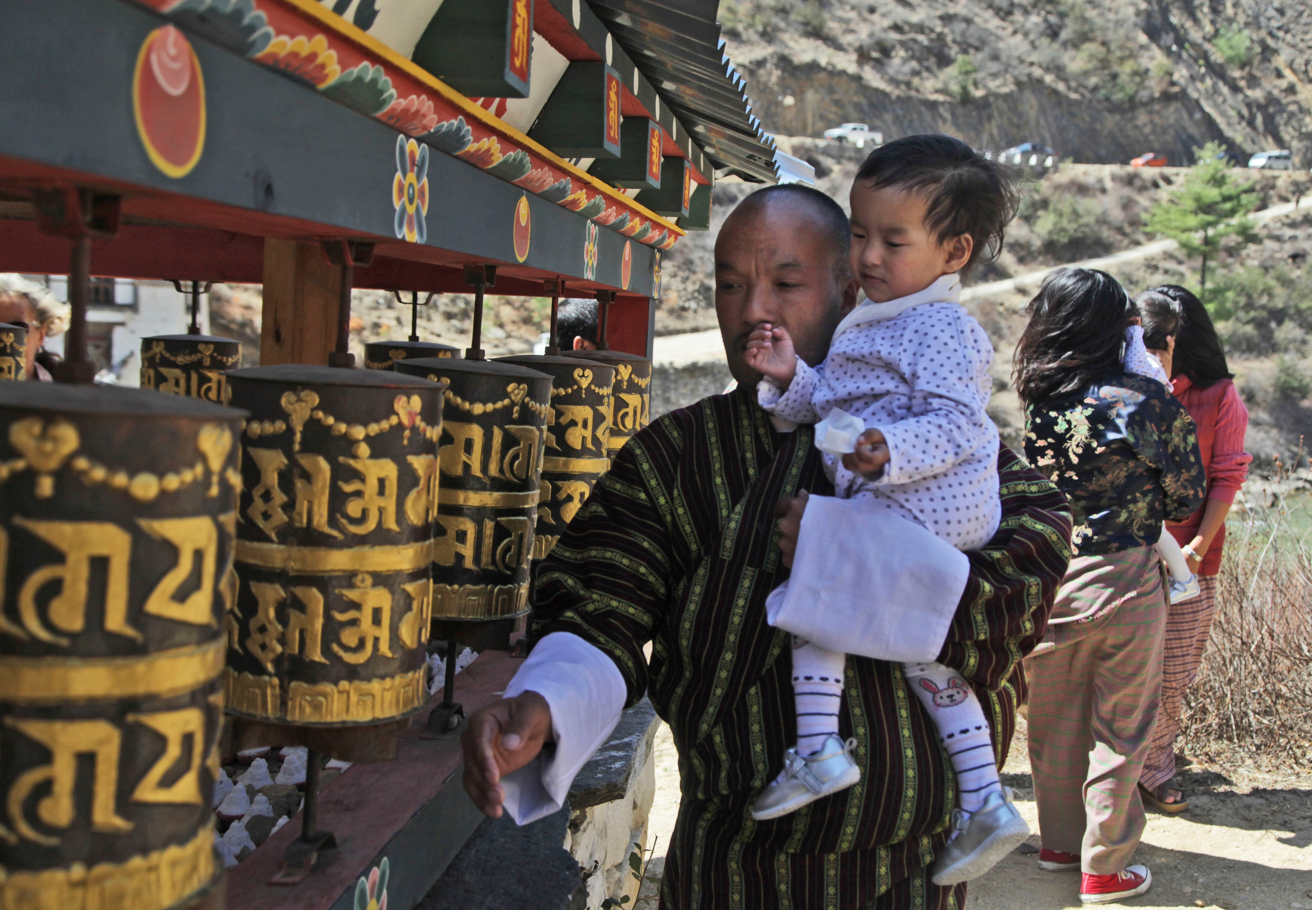 Sonam Tshering holds one of his conjoined twin daughters and spins prayer wheels at the Tachog Lhakhang Buddhist temple.