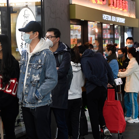 People line up to enter a supermarket hours before a citywide curfew is introduced in Melbourne, Sunday, 2 August, 2020.