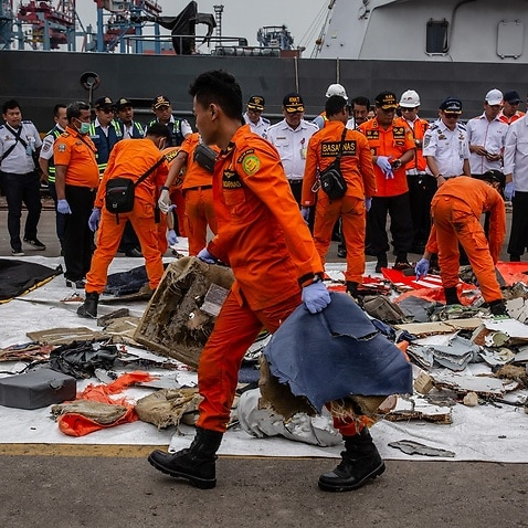 Search and Rescue personnel examine recovered debris.
