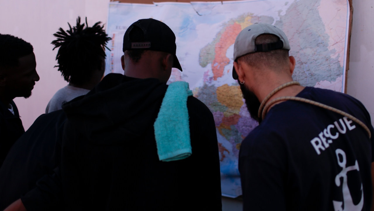 Men look at a map of Europe aboard the Ocean Viking in the Mediterranean Sea.