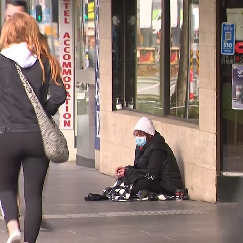 A homeless woman wearing a mask in Melbourne.