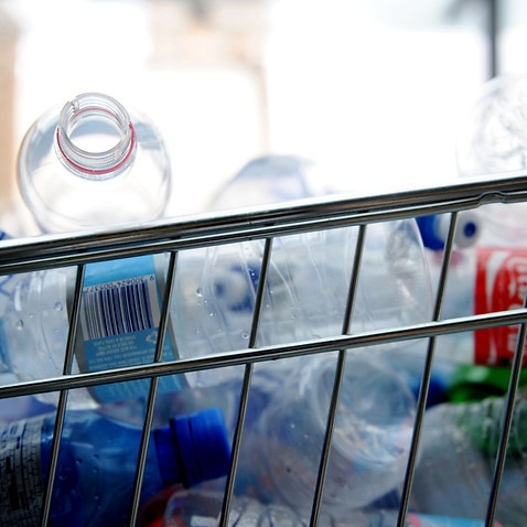 Empty plastic bottles are packed into trolleys (AAP).