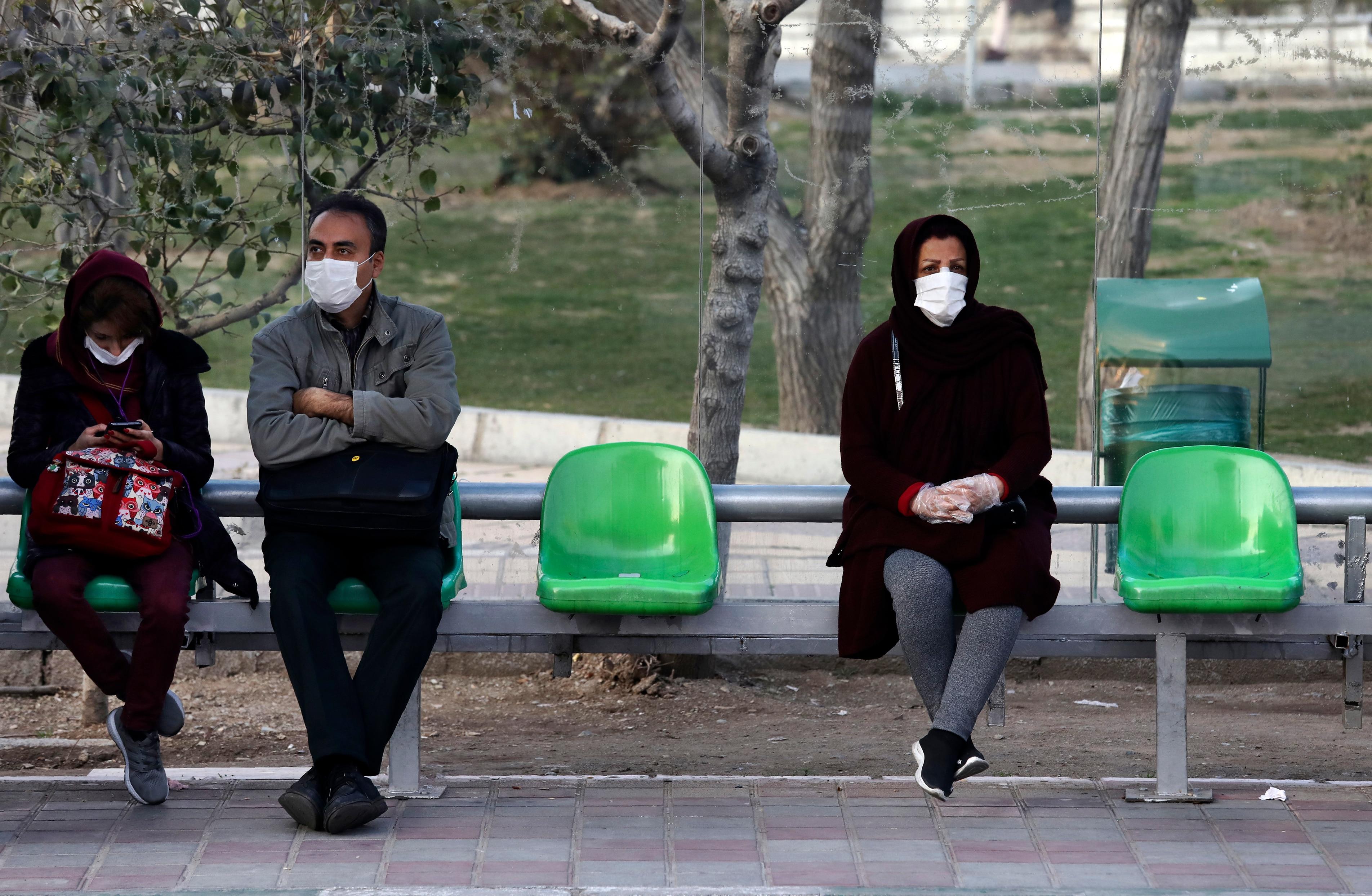 People wearing face masks wait for bus in a bus stop in a street in western Tehran, Iran.