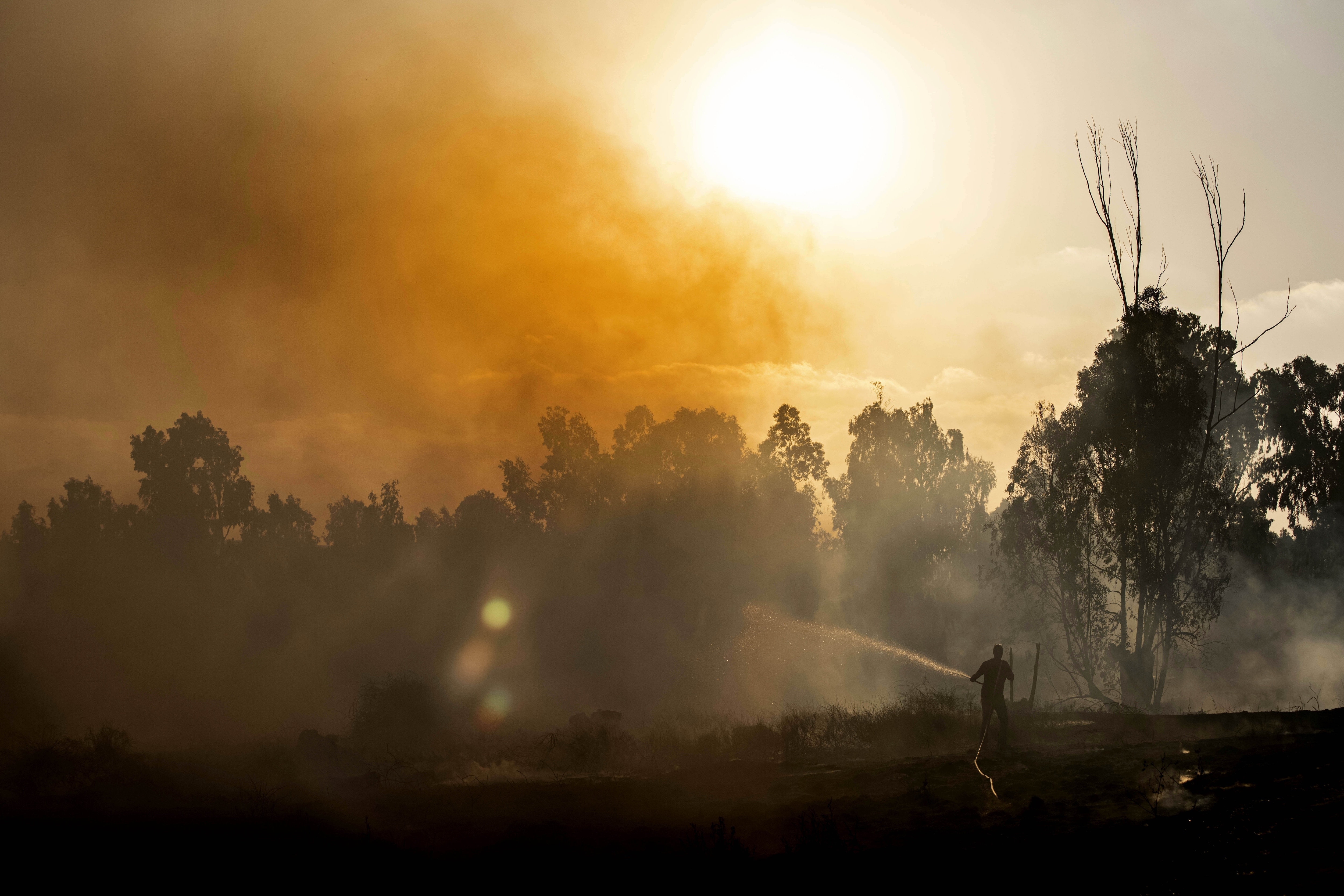 A man works at the site of a fire on the Israeli side of the border between Israel and Gaza